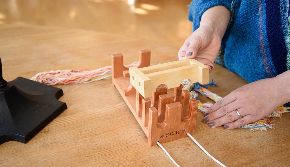 タテ糸を重りで押さえ、綾ホルダーの準備をします。