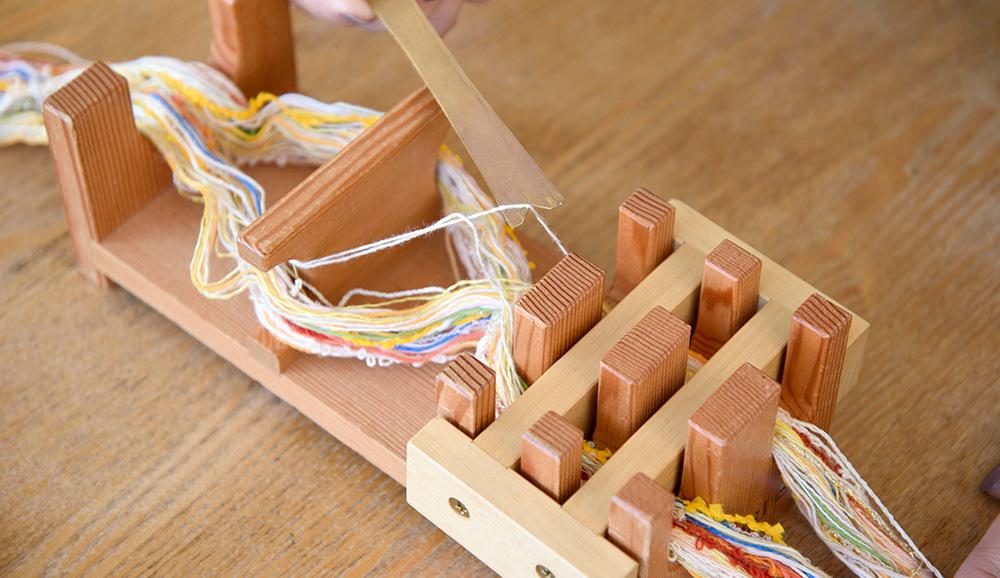 専用オモリを取り付けたら、綾の部分から筬通し板を使い、糸を1本だけ引き出し、筬に通します。