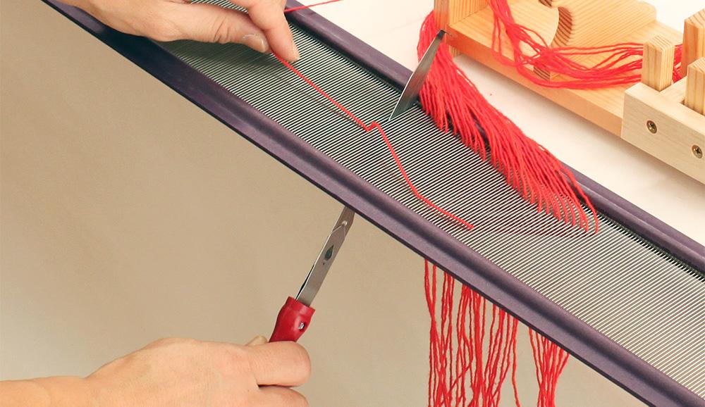 デンチングフック…タテ糸を筬目に対して直角に置き、デンチングフックを横の切れ目に色をひっかけ下まで引きおろすと、自動的に隣の目に移ります。