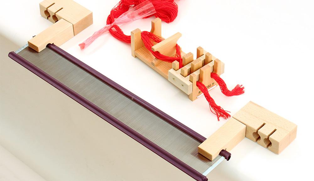 筬の両端に、経通台の穴を差し入れ、筬がテープルの端から手前に出ている状態にします。
