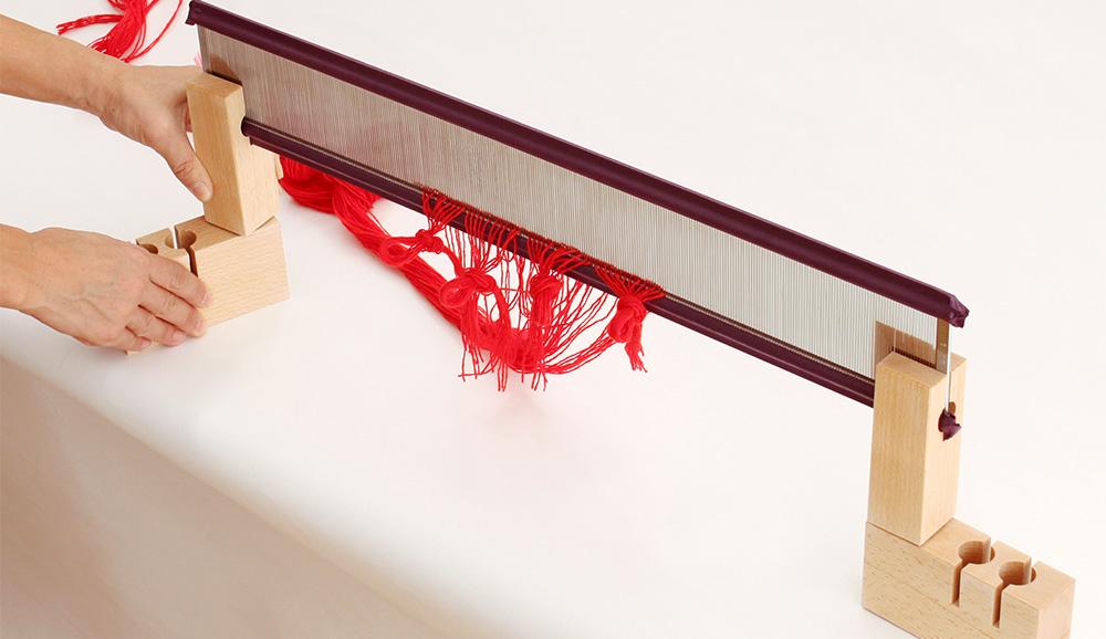 筬通しが完了したら、経通台を筬ごと自立させ、経通台の下部を綜絖枠用の穴が手間にくるまで回転させます。