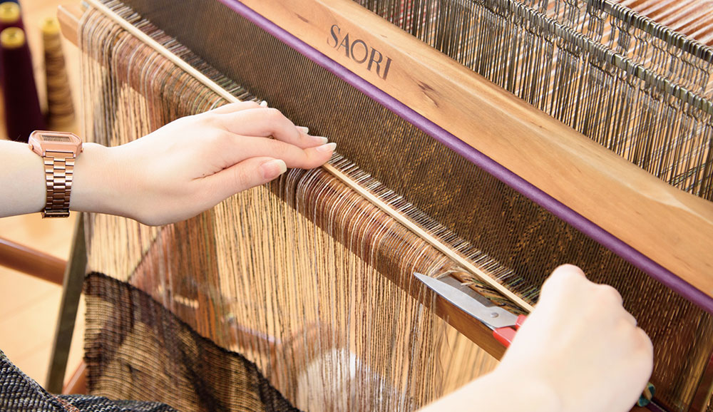 くさび板を押さえながらタテ糸を切ります。