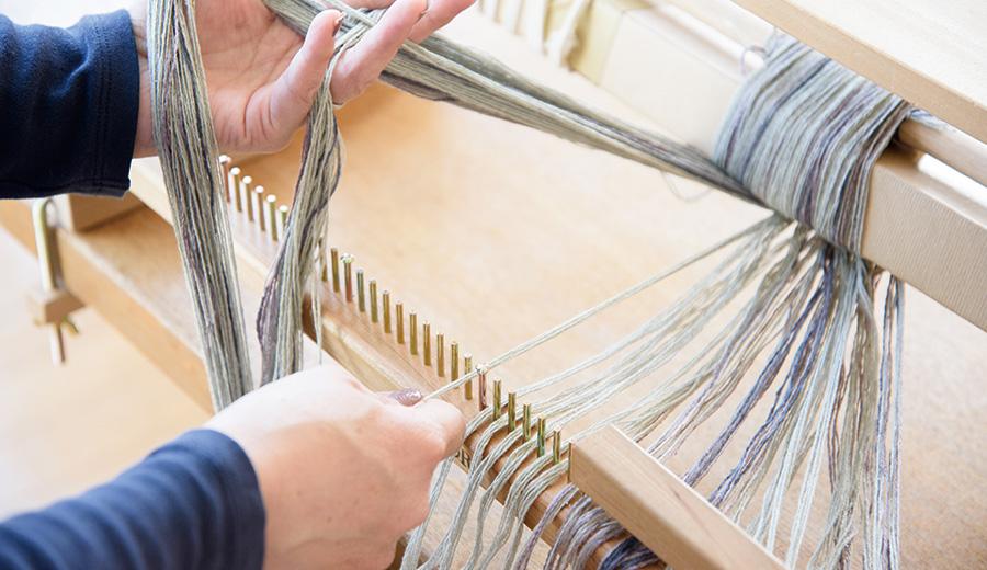 研三整経で使用する分配筬をセットし、糸掛けで作った綾の束を一束ずつ配置します。タテ糸ローラーが近いので、楽に配置することができます。