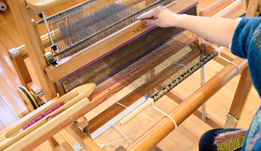 ボビンをスピンドルに差し入れ、ワインダーのハンドルを回して糸を巻きます。